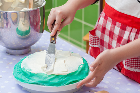 a hand spreading whipped cream on crape cake Stock Photo - 26345849