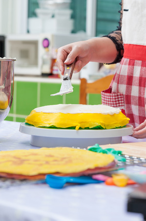 a hand spreading whipped cream on crape cake Stock Photo - 26345850