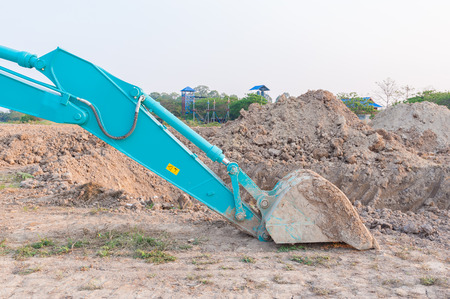 excavator bucket on crushed soil, building site photo