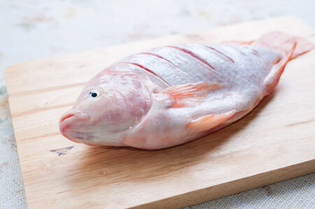 nilotica: Red fish (Tilapia nilotica) on wood chopping board in kitchen. Stock Photo