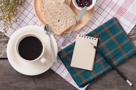 Memo pad with bread and a cup of coffee on table. photo