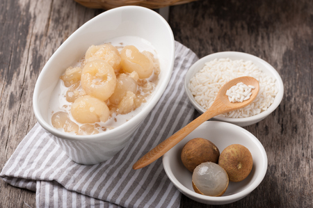 Sticky rice boiled in syrup with longan and coconut milk dressing. Thai dessert photo