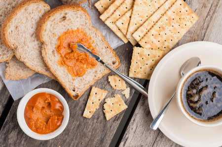 Sliced whole wheat bread with crackers, coffee and Thai tea cream on table. photo