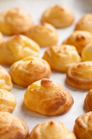 profiterole: Choux cream in bakery tray on wood table. Stock Photo