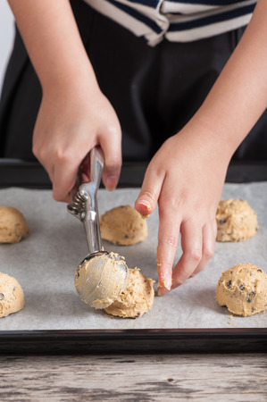 Putting mixed cookie ingredients into tray photo