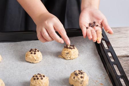 Adding chocolate chip to raw cookie photo