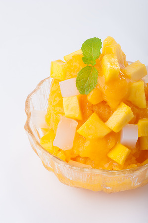 Mango flavoured shave ice with pieces of mango and coconut jelly.