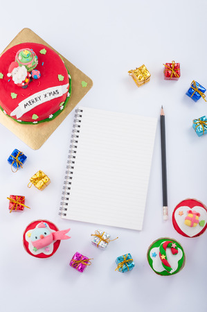 Christmas concept fodant cake with blank notebook and pencil on white table. photo