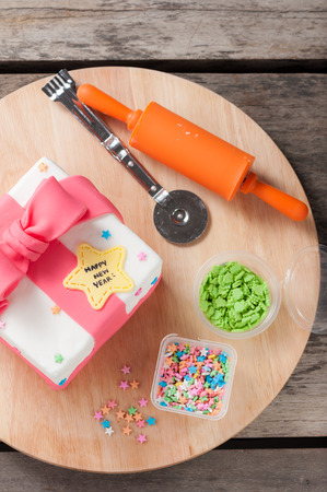 fondant fancy: New year present concept fodant cake on wood table. Stock Photo