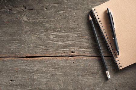 Small notepad with pen and pencil on rustic wood background with low key scene. photo