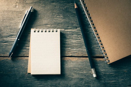 pen and paper: Small notepad with pen and pencil on rustic wood background with film filter effect