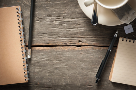 Small notepad with empty coffee cup, tea bag, pen and pencil on rustic wood background with low key scene photo
