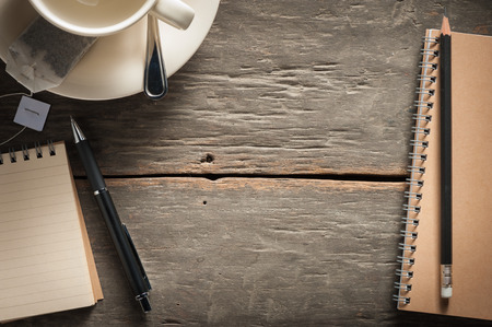 Small notepad with empty coffee cup, tea bag, pen and pencil on rustic wood background with low key scene Stock Photo