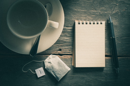 tea filter: Small notepad with empty coffee cup, tea bag, pen and pencil on rustic wood background with film filter effect Stock Photo