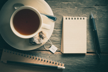tea filter: Small notepad with a cup of tea, pen and pencil on rustic wood background with film filter effect