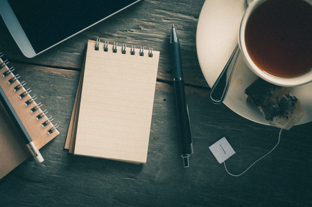 Small notepad with a cup of tea, pen, pencil and cellphne on rustic wood background with film filter effect photo
