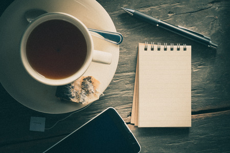 tea filter: Small notepad with a cup of tea, pen, pencil and cellphne on rustic wood background with film filter effect Stock Photo