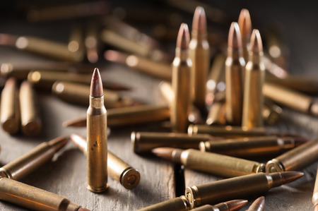 m16 ammo: Rifle bullets on wood table with low key scene Stock Photo