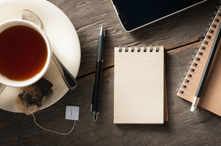 Small notepad with a cup of tea, pen, pencil and cellphne on rustic wood background with low key scene photo
