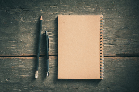 paper and pen: Small notepad with pen and pencil on rustic wood background with film filter effect