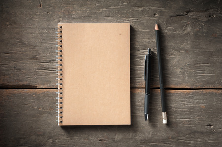 Small notepad with pen and pencil on rustic wood background with low key scene.