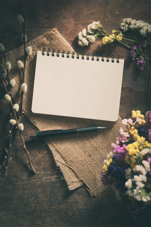 Small notepad with pen and pencil on rustic wood background with film filter effect Stock Photo - 39376516