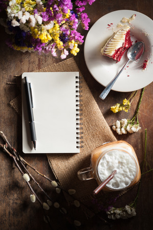 Notepad with pen, a glass of Thai tea and bits of red velvet cake on rustic wood background with low key scene photo