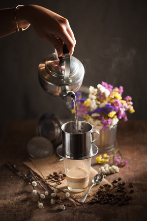 coffee filter: Vietnamese style drip coffee, Woman hand pouring hot water into metal coffee filter with low key scene