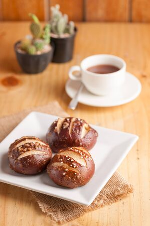 lye: Freshly baked soft pretzel with generous sprinkling of coarse salt on white dish and a cup of hot chocolate in background Stock Photo
