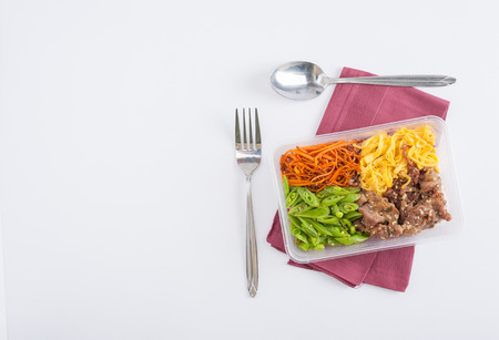 Bibimbub in clean food style. Brown rice with roasted pork, egg, and vegetables on white table Stock Photo