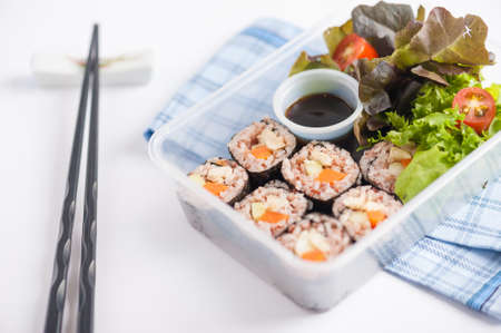delivery box: Japanese style brown rice maki with grilled chicken, grilled pork, and grilled tofu cooked by clean food concept in lunch box on white table