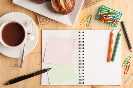 note notebook: Notebook and sticky paper, paper clip, color pencil, and pen on wood table in vintage style Stock Photo