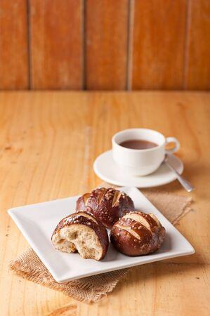 하얀 접시에 굵고 소금과 관대 한 뿌리와 갓 구운 소프트 프레첼과 배경에 핫 초콜릿 한잔