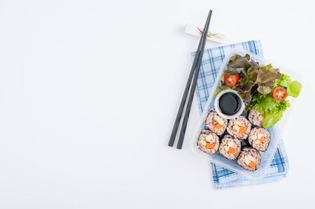 Japanese style brown rice maki with grilled chicken, grilled pork, and grilled tofu cooked by clean food concept in lunch box on white table Stock Photo - 41987489
