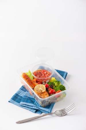 clean food: Grilled salmon with tomato salsa and salad cooked by clean food concept in lunch box on white table