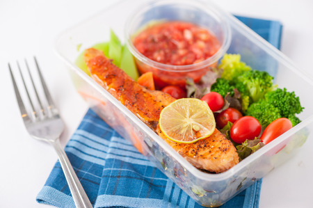 meal: Grilled salmon with tomato salsa and salad cooked by clean food concept in lunch box on white table