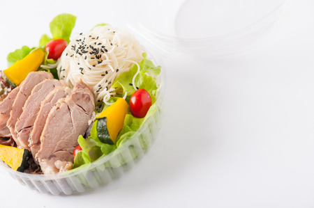 lunch table: Salad with roasted pork and soba noodles by clean food concept in lunch box on white table