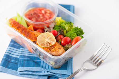 food box: Grilled salmon with tomato salsa and salad cooked by clean food concept in lunch box on white table