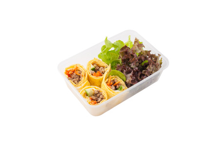 clean food: Thai spicy egg rolls (Fresh spring rolls, Kuay Teaw Lui Suan but use egg replace to rice sheet) with tofu, minced pork and vegetables cooked by clean food concept in lunch box isolated on white background