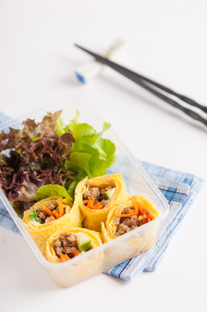 lunch table: Thai spicy egg rolls (Fresh spring rolls, Kuay Teaw Lui Suan but use egg replace to rice sheet) with tofu, minced pork and vegetables cooked by clean food concept in lunch box on white table Stock Photo