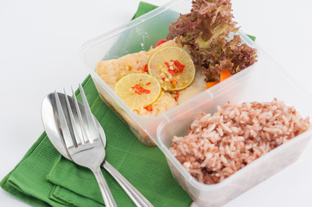 food concept: Thai style steamed fish in spicy lemon sauce cooked by clean food concept with vegetables and brown rice in lunch box on white table