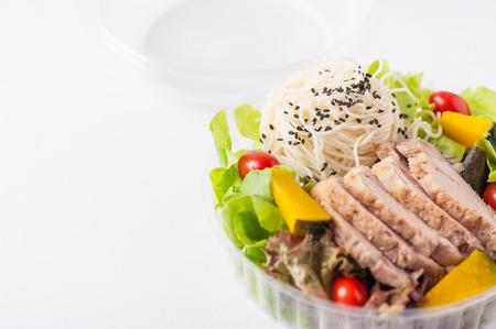 Salad with roasted pork and soba noodles by clean food concept in lunch box on white table