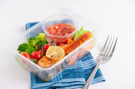 clean: Grilled salmon with tomato salsa and salad cooked by clean food concept in lunch box on white table