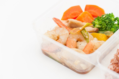 clean food: Thai style spicy stir fried shrimps cooked by clean food concept with brown rice and vegetables in lunch box on white table