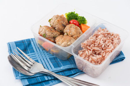 traditional food: Thai style fried pork ball cooked by clean food concept with vegetables and brown rice in lunch box on white table