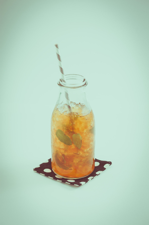tea filter: Iced peppermint toffee tea in glass bottle with striped straw garnished with mint leaves with film filter effect