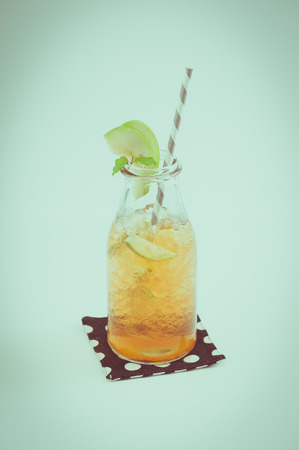 tea filter: Iced apple tea in glass bottle with striped straw garnished with green apple and mint leaf with film filter effect