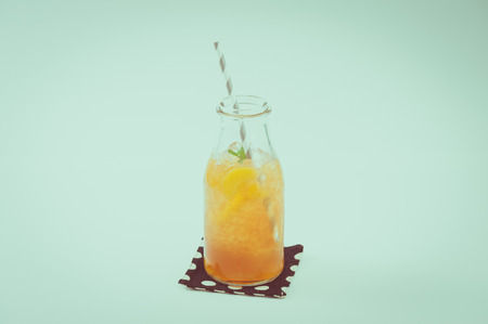 tea filter: Iced peach tea garnished with mint leaves in glass bottle with striped straw with film filter effect Stock Photo