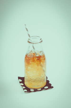 tea filter: Iced carramel tea in glass bottle with striped straw with film filter effect