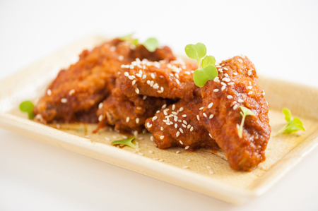 Korean fusion style deep fried chicken wings seasoned with Korean spicy kimchi sauce on square ceramic dish